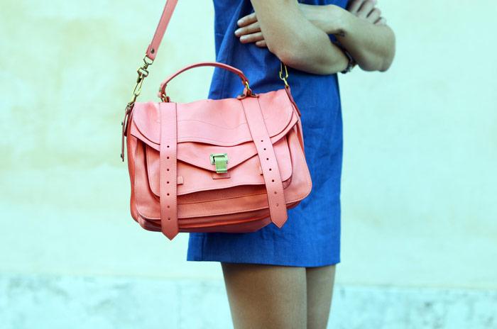 femme portant un sac rose avec une robe bleu