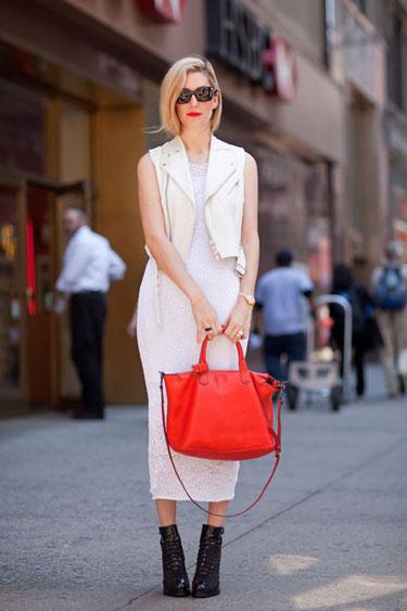 femme blonde portant un sac rouge avec un robe blanche